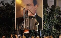 In this Jan. 25, 2011 file photo, demonstrators deface a poster of Egyptian President Hosni Mubarak in Alexandria, Egypt. (AP Photo)