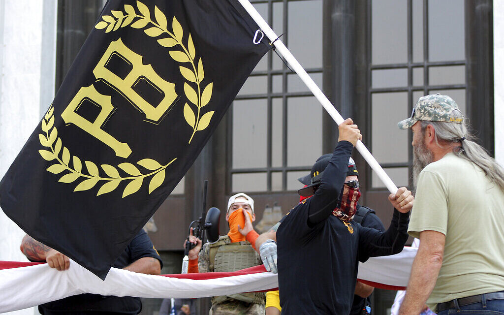 In this September 7, 2020, file photo, a protester carries a Proud Boys banner, a right-wing group, while other members start to unfurl a large US flag in front of the Oregon State Capitol in Salem, Oregon. (AP Photo/Andrew Selsky, File)