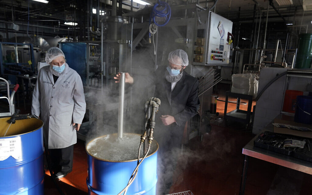 Rabbis Joseph Schwartz, left, and Mendel Einhorn kosherize equipment in boiling water as they help Hanan Products prepare for their kosher-for-Passover production run on Jan. 7, 2021, in Hicksville, N.Y. (AP Photo/Seth Wenig)