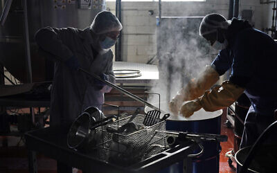 Rabbi Joseph Schwartz, left, and Ryan Eleazar use boiling water to kosherize equipment for the Hanan Products' kosher-for-Passover production run on Jan. 7, 2021.  (AP/Seth Wenig)