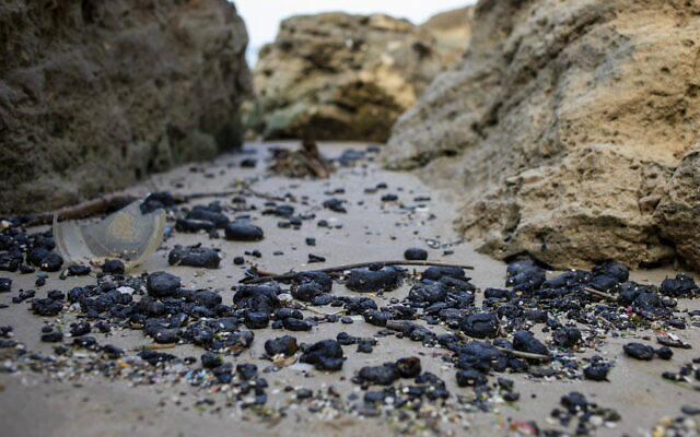 Pieces of tar from an oil spill in the Mediterranean Sea wash up on a beach in the Gdor Nature Reserve near Michmoret, Israel, Monday, March 1, 2021. The cleanup from the disastrous oil spill that has blackened most of the country's shoreline is expected to take months. (AP Photo/Ariel Schalit)