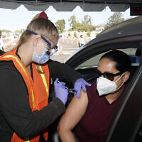 Vanessa Guerra (right), a special education teacher, receives a shot of the Moderna COVID-19 vaccine from nurse Kelly Mendoza, in Inglewood, California, March 2, 2021. (AP Photo/Marcio Jose Sanchez)