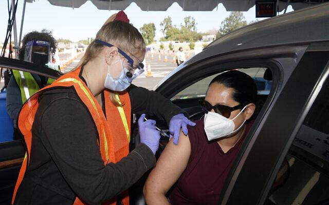 Vanessa Guerra (right), a special education teacher, receives a shot of the Moderna COVID-19 vaccine from nurse Kelly Mendoza, in Inglewood, California, March 2, 2021. (AP Photo/Marcio Jose Sanchez)