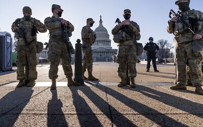 """Members of the Michigan National Guard and the US Capitol Police keep watch as heightened security remains in effect around the Capitol grounds since the Jan. 6 attacks by a mob of supporters of then-President Donald Trump, in Washington, Wednesday, March 3, 2021. The US Capitol Police say they have intelligence showing there is a """"possible plot"""" by a militia group to breach the Capitol on Thursday. (AP Photo/J. Scott Applewhite)"""