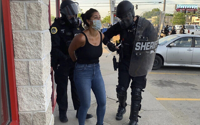 Police officers are shown arresting Des Moines Register reporter Andrea Sahouri after a Black Lives Matter protest she was covering on May 31, 2020, in Des Moines, Iowa, was dispersed by tear gas. (Katie Akin via AP)