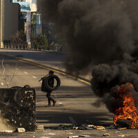 Protesters burn tires to close the main road, after the Lebanese pound hit a record low against the dollar on the black market, in Beirut, Lebanon on March 6, 2021. (AP/Hassan Ammar)