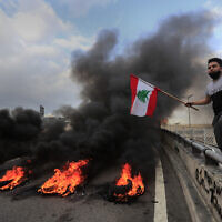 A protester waves a Lebanese flag near burning tires set to block a main highway, during a protest in the town of Jal el-Dib, north of Beirut, Lebanon, Monday, March 8, 2021. (AP Photo/Hussein Malla)