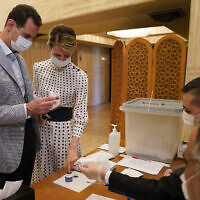This file photo released July 19, 2020, on the official Facebook page of the Syrian Presidency shows Syrian President Bashar Assad, left, and his wife Asma voting at a polling station in the parliamentary elections, in Damascus, Syria. (Syrian Presidency via AP)