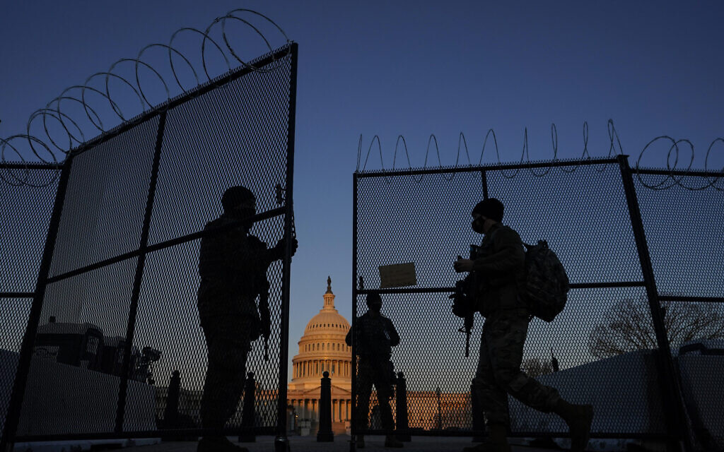 National Guard open a gate in the razor wire topped perimeter fence around the Capitol allow another member in at sunrise in Washington, March 8, 2021. (AP Photo/Carolyn Kaster)