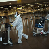 Passengers, wearing full protective gear to protect against the spread of coronavirus, push their luggage to a check-in counter at Zaventem international airport in Brussels, July 29, 2020. (AP Photo/Francisco Seco, File)