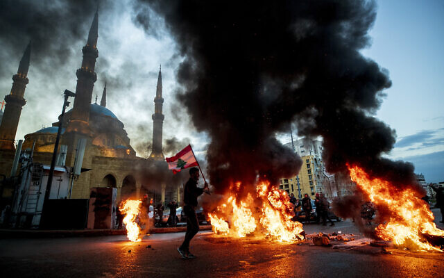 Mounir Hujairi, 23, holds up a Lebanese national flag as walks in front of burning tires set on fire to block a main road, during a protest in downtown Beirut, Lebanon, March 3, 2021. (AP Photo/Hassan Ammar, File)