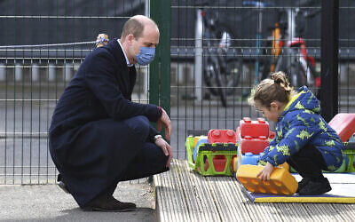 Britain's Prince William watches a child in the playground during a visit with Kate, Duchess of Cambridge, to School21, a school in east London, March 11, 2021. (Justin Tallis/Pool via AP)