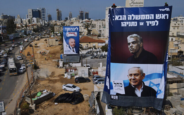 Workers hang an election campaign billboard for the Likud Party showing a portrait of its leader Prime Minister Benjamin Netanyahu, lower right, and opposition party leader Yair Lapid, upper right, next to a billboard of the Yisrael Beitenu Party showing its leader Avigdor Lieberman, in Bnei Brak, Sunday, March. 14, 2021. (AP Photo/Oded Balilty)
