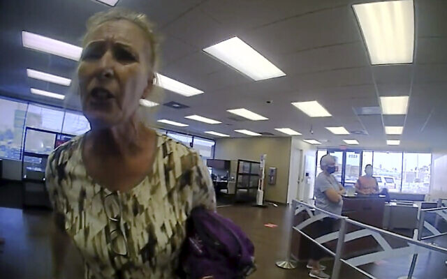 This frame grab from police body cam video provided by the Galveston Police Department, in Galveston, Texas, shows Terry Wright, 65, of Grants Pass, Oregon, arguing with an officer inside a Bank of America branch, in Galveston, March 11, 2021, (Galveston Police Department via AP)