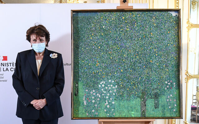 French Culture Roselyne Bachelot poses next to an oil painting by Gustav Klimt painted in 1905 called 'Rosebushes under the Trees,' during a ceremony at the Orsay museum in Paris, March 15, 2021. (Alain Jocard/Pool Photo via AP)