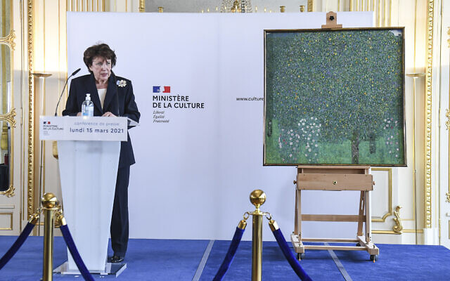 French Culture Minister Roselyne Bachelot poses next to an oil painting by Gustav Klimt painted in 1905 called 'Rosebushes under the Trees,' during a ceremony at the Orsay museum in Paris, March 15, 2021. (Alain Jocard/Pool Photo via AP)
