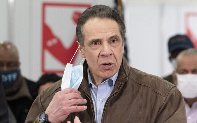 New York Gov. Andrew Cuomo removes his mask during a visit to a COVID-19 vaccination site, Monday, March 15, 2021, at the State University of New York in Old Westbury. The site is scheduled to open on Friday. (AP Photo/Mark Lennihan, Pool)