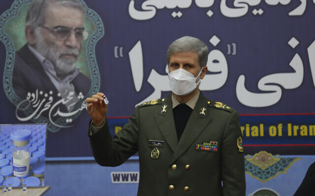 In this photo released by the official website of the Iranian Defense Ministry on March 16, 2021, Defense Minister Gen. Amir Hatami shows a vial of the homegrown Fakhra coronavirus vaccine at a staged event in Tehran, Iran. The vaccine is named after chief Iranian nuclear scientist Mohsen Fakhrizadeh, shown in a banner at rear, who was killed in a November 2021 attack that Iran blamed on Israel. (Iranian Defense Ministry via AP)