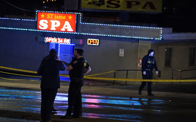 Law enforcement officials confer outside a massage parlor following a shooting on March 16, 2021, in Atlanta. (AP Photo/Brynn Anderson)