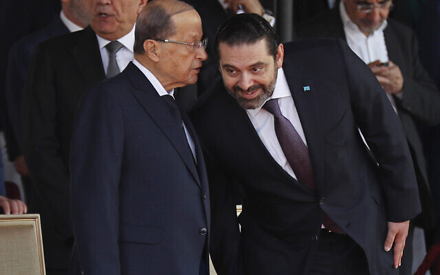 In this Nov. 22, 2018 file photo, Lebanese President Michel Aoun, left, whispers to Prime Minister Saad Hariri, during a military parade to mark the 75th anniversary of Lebanon's independence from France, in downtown Beirut, Lebanon. Lebanon's president called Wednesday, March 17, 2021 on the prime minister-designate to form a government immediately or step aside as the country plunges deeper into economic crisis. (AP Photo/Hussein Malla, File)