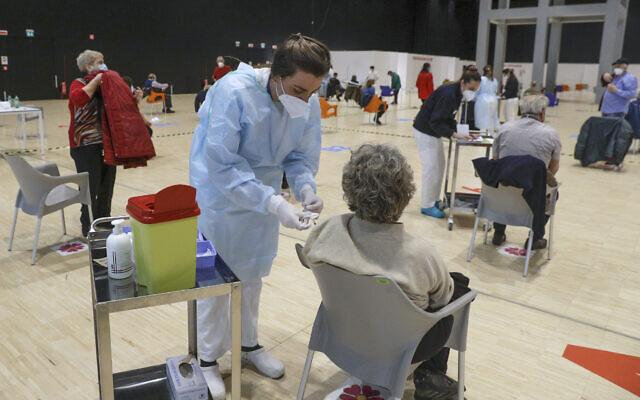 Medical staff administer the AstraZeneca vaccine at La Nuvola convention center in Rome, March 19, 2021. (AP Photo/Gregorio Borgia)
