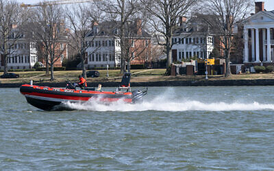 A District of Columbia Fire Boat checks buoys in the waterway next to Fort McNair, seen in background in Washington. March 19, 2021. (AP Photo/Jacquelyn Martin)