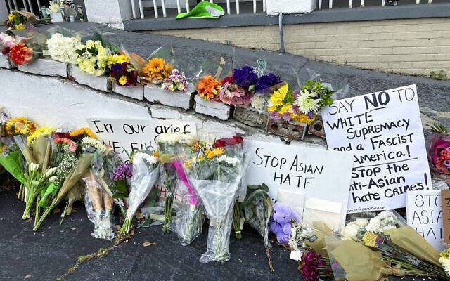 On March 19, 2021, flowers, candles and signs are displayed at a makeshift memorial in Atlanta. A deadly rampage at three Georgia massage businesses, where the employees were mostly of Asian descent, has prompted Asian American women to openly share stories of being sexually harassed or demeaned based on their race. (AP Photo/Candice Choi, File)