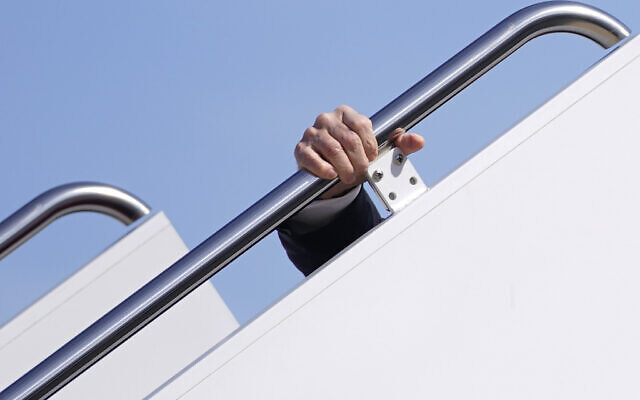 US President Joe Biden holds onto the hand rail as he stumbles while boarding Air Force One at Andrews Air Force Base, Md., Friday, March 19, 2021. Biden is en route to Georgia. (AP Photo/Patrick Semansky)