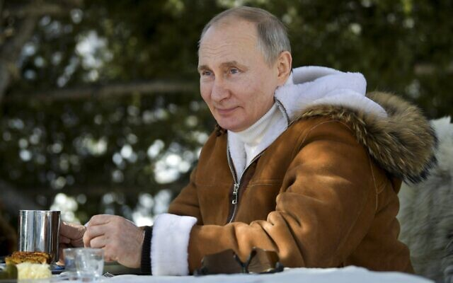 In this photo made available on March 21, 2021, Russian President Vladimir Putin drinks during a break in a taiga forest in Russia's Siberian region. (Alexei Druzhinin, Sputnik, Kremlin Pool Photo via AP)