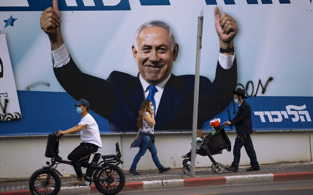 People pass an election campaign billboard for the Likud party that shows a portrait of its leader, Prime Minister Benjamin Netanyahu, in Ramat Gan, Israel, March 21, 2021. Israelis head to the polls on Tuesday for what will be the fourth parliamentary election in just two years. Once again, the race boils down to a referendum on Netanyahu. (AP Photo/Oded Balilty)