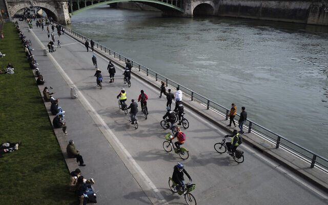 French police officers ride among Parisian bikers on the banks of the Seine river in Paris, March 21, 2021. (AP Photo/Francois Mori)