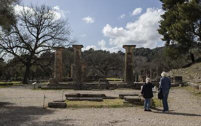 Tourists stand in front of the temple of Hera in ancient Olympia, the place that hosted the ancient Olympic Games, on Monday, March 22, 2021. Greece's government reopened the ancient sites nationwide after four months as it prepares to restart the tourism season in mid-May. (AP Photo/Petros Giannakouris)