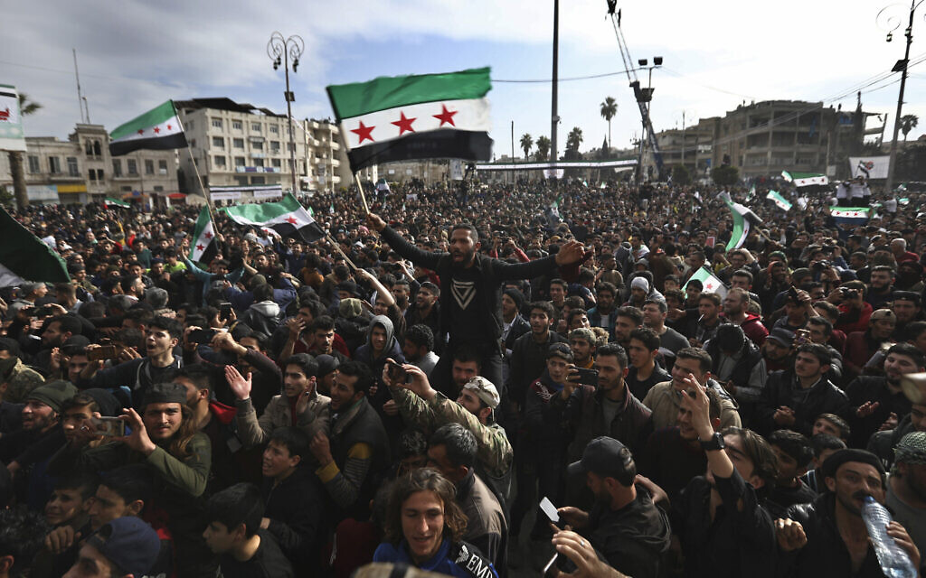 Thousands of anti-Syrian government protesters shout slogans and wave revolutionary flags, to mark 10 years since the start of a popular uprising against President Bashar Assad's rule, in Idlib, the last major opposition-held area of the country, in northwest Syria, March 15, 2021. (Ghaith Alsayed/AP)