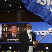 Prime Minister Benjamin Netanyahu's supporters wave Likud party flags after first exit poll results for the Israeli elections at his party's headquarters in Jerusalem, Tuesday, March. 23, 2021. (AP Photo/Ariel Schalit)