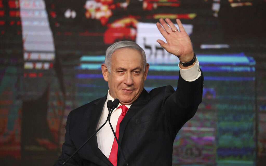 Prime Minister Benjamin Netanyahu waves to his supporters after the first exit poll results for Knesset elections at his Likud party's headquarters in Jerusalem, March 24, 2021. (AP Photo/Ariel Schalit)