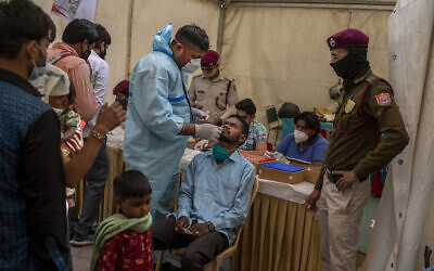 A health worker takes a nasal swab sample of a passenger to test for coronavirus at a bus terminal in New Delhi, India, Wednesday, March 24, 2021. (AP Photo/Altaf Qadri)