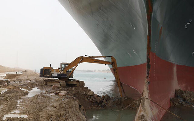 A work crew using excavating equipment tries to dig out the Ever Given, a Panama-flagged cargo ship, that is wedged across the Suez Canal and blocking traffic in the vital waterway. (Suez Canal Authority via AP)
