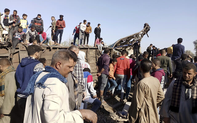 Egyptians look for remains of victims around mangled train carriages at the scene of a train accident in Sohag, Egypt, March 26, 2021. (AP Photo)