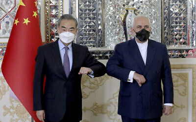 Iranian Foreign Minister Mohammad Javad Zarif, right, and his Chinese counterpart Wang Yi, pose for photos at the start of their meeting in Tehran, Iran, March 27, 2021. Iran and China on Saturday signed a 25-year strategic cooperation agreement addressing economic issues amid crippling US sanctions on Iran, state TV reported. (AP Photo/Ebrahim Noroozi)