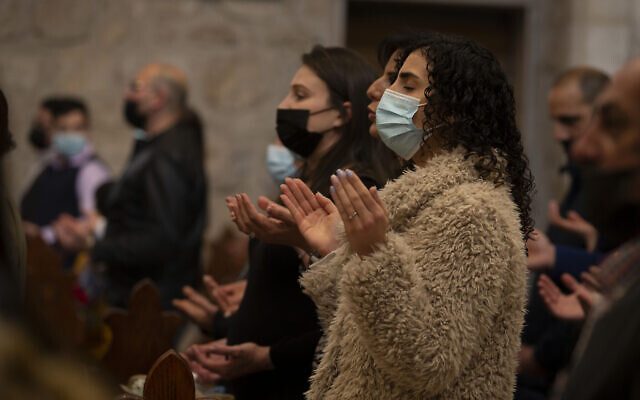 People attend a mass on a Palm Sunday at the Church of the Nativity, traditionally believed to be the birthplace of Jesus Christ, in the West Bank city of Bethlehem, Sunday, March 28 2021. (AP Photo/Majdi Mohammed)