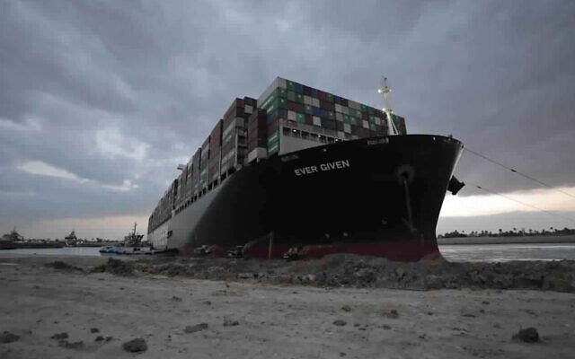 In this photo released by the Suez Canal Authority, tug boats and diggers work to free the Panama-flagged, Japanese-owned Ever Given, which is lodged across the Suez Canal, March 28, 2021. (Suez Canal Authority via AP)