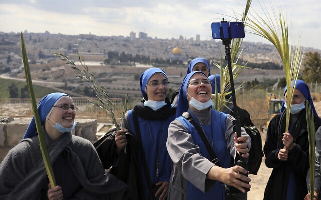 Nuns pose for a selfie as they mark Palm Sunday on the Mount of Olives in Jerusalem, March 28, 2021. (AP Photo/ Mahmoud Illean)