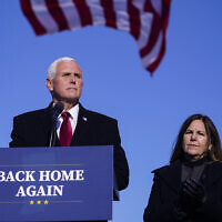 FILE - In this Jan. 20, 2021, file phot, former Vice President Mike Pence speaks after arriving back in his hometown of Columbus, Ind., as his wife Karen watches. (AP Photo/Michael Conroy, File)