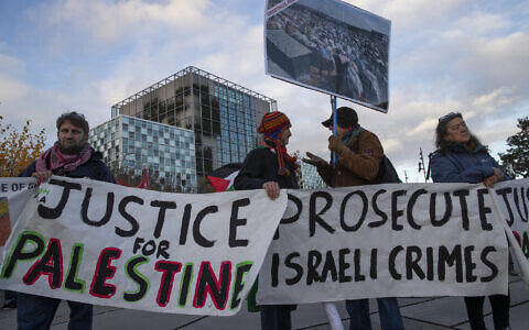 Demonstrators carry banners outside the International Criminal Court, ICC, rear, urging the court to prosecute Israel's army for war crimes in The Hague on Nov. 29, 2019. (AP/Peter Dejong)