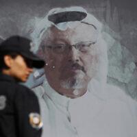 In this Oct. 2, 2019, photo, a Turkish police officer walks past a picture of slain Saudi journalist Jamal Khashoggi near the Saudi Arabia consulate in Istanbul (AP Photo/Lefteris Pitarakis, File)
