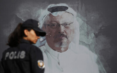 In this Oct. 2, 2019, photo, a Turkish police officer walks past a picture of slain Saudi journalist Jamal Khashoggi near the Saudi Arabia consulate in Istanbul (AP Photo/Lefteris Pitarakis, File)