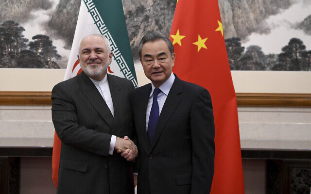 China's Foreign Minister Wang Yi, right, shakes hands with Iran's Foreign Minister Mohammad Javad Zarif during a meeting at the Diaoyutai state guest house in Beijing, December 31, 2019. (Noel Celis/Pool Photo via AP)