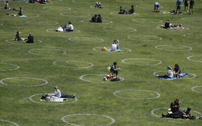 Visitors set up inside circles designed to help prevent the spread of the coronavirus by encouraging social distancing, at Dolores Park in San Francisco, June 28, 2020. (AP Photo/Jeff Chiu)