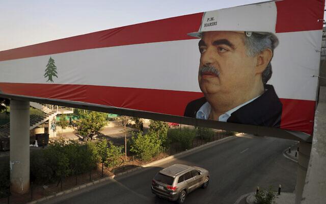 A car passes under a Lebanese flag with a picture of slain former Lebanese Prime Minister Rafik Hariri in Beirut, Lebanon, Tuesday, Aug. 18, 2020. (AP Photo/Bilal Hussein)