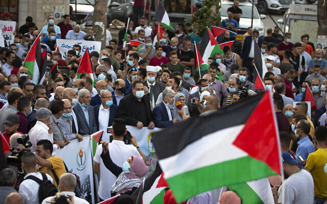 Palestinians wave national flags during a protest against normalization of ties between the United Arab Emirates and Bahrain with Israel, in the West Bank city of Ramallah, September 15, 2020. (Majdi Mohammed/AP)